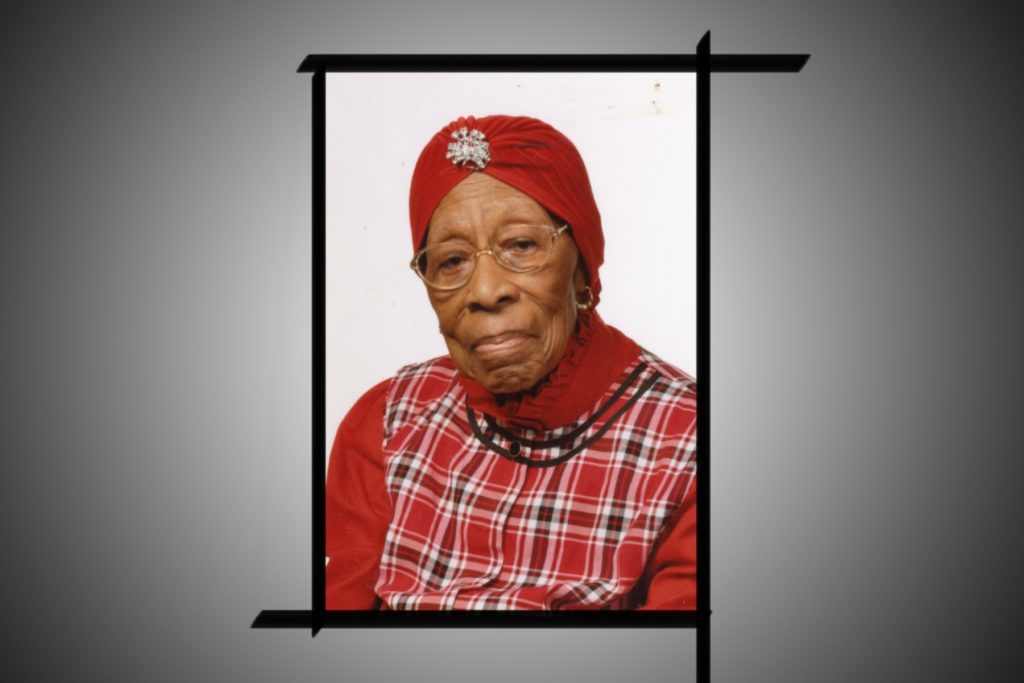 Still photograph of Grandmother Taylor, wearing a red plaid tunic, red turtleneck, and red turban with a jewel in the middle