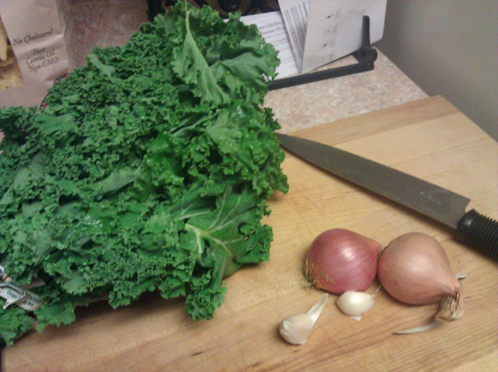 Picture of kale, shallots, garlic, and a chef's knife on a cutting board in my kitchen