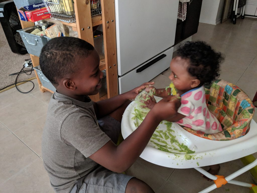 Picture of my son, Khaden, feeding his toddler cousin peas in a baby chair